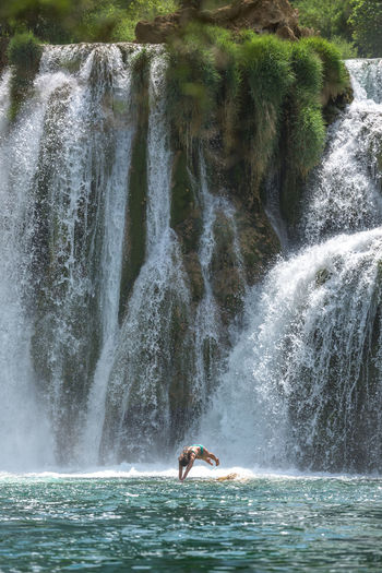 Woman diving in pond against waterfall at forest
