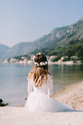 Rear view of bride sitting on sand by bay against sky