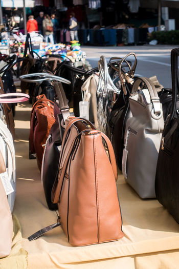 Women's handbags exposed for sale on a stall in the outdoor market. Bag Day Still Life No People Focus On Foreground Luggage Backpack Large Group Of Objects Sunlight Table Absence Outdoors Personal Accessory Business Suitcase Purse Shoe Arrangement Travel Leather