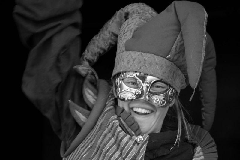 Portrait of smiling girl wearing mask against black background