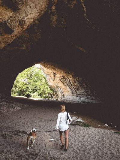 Rear view full length of woman with dog on sand entering cave
