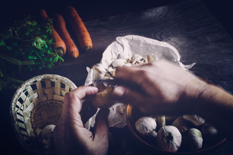 Cropped image of chef peeling mushroom on table