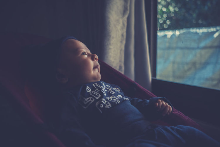 Close-up of boy relaxing in baby carriage at home