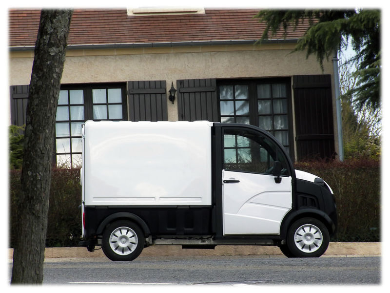 Utility French Aixam model behind house frontage Aixam Car Aixam TM D-Truck Utility Car D Truck Mode Of Transportation Made In France Motor Vehicle Profil White And Black Colors Car House Trees Day White Frame In France