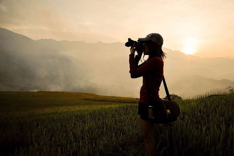 Female Photographer Taking Pictures In Field