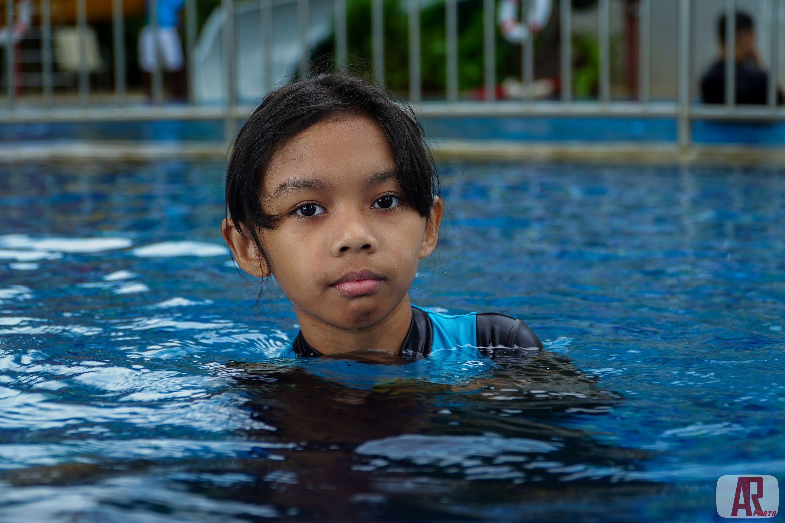 portrait, pool, child, swimming pool, childhood, headshot, swimming, water, one person, leisure activity, real people, boys, lifestyles, looking at camera, waterfront, girls, males, innocence, outdoors