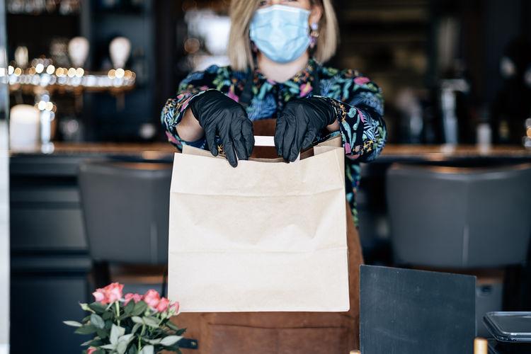 Woman at the restaurant door holding paper food bag - takeaway in coronavirus outbreak time