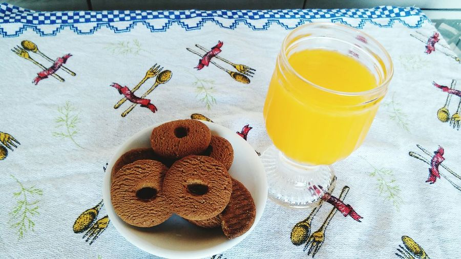 High Angle View Of Fresh Cookies And Orange Juice Served On Table