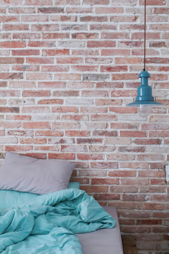 Industrial design of cozy bedroom with bed,blue lamp and brick wall Wall Brick Wall Wall - Building Feature Brick Furniture Domestic Room Pillow Indoors  Architecture Built Structure Relaxation Lighting Equipment Day Pattern Bed No People Lifestyles Bedroom Absence Electric Lamp Duvet Elegant Lamp Blanket Bed Pillow Blue Lamp Posts Brick Wall Design Modern Modern Architecture Apartment Wall Room Decor Room Bedtime Home Home Interior Interior Interior Design Cozy Cozy Place Flat Simple Plant Hotel Comfortable Decor Bedsheets Cushion House Lightbulb Bedside  ArtWork Minimalism Living Decoration Loft Loft Style Space