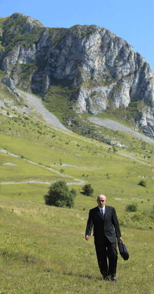 Businessman walking on grass near rocky mountains. Business Man Scenic Black Suit Businessman Concept Field Grass Landscape Lifestyles Mountain Mountain Range Nature One Man Only One Person Outdoors People Real People Scenics Strategy Suit Walking Well-dressed