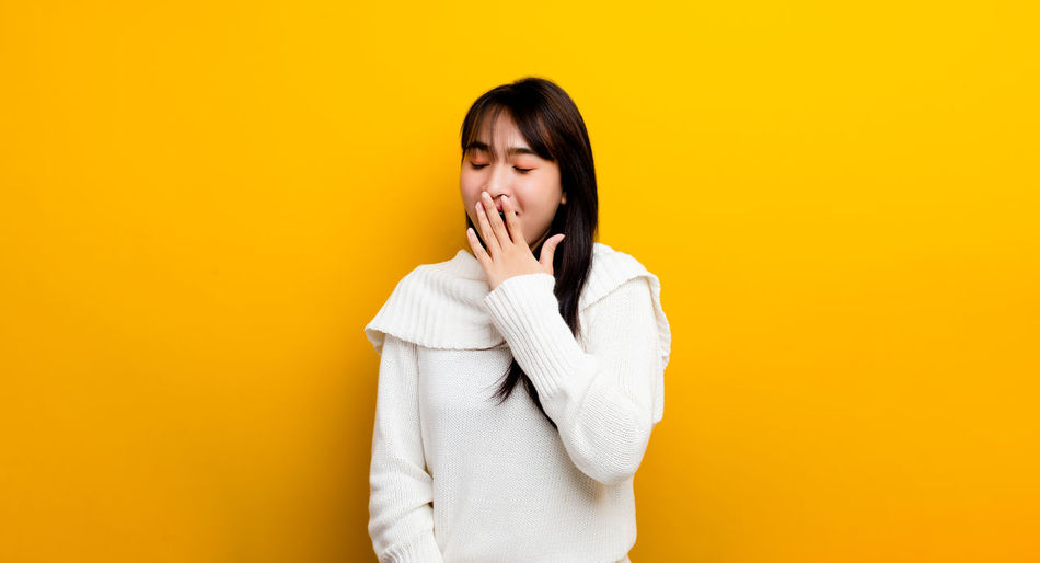 Portrait of a beautiful young woman over yellow background