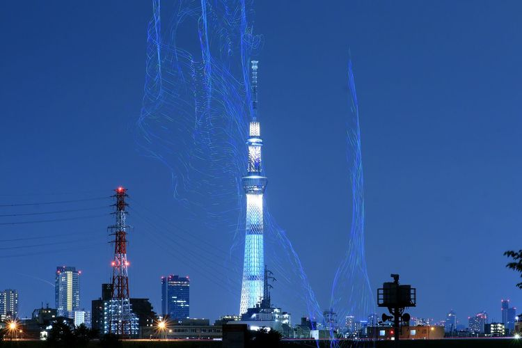 Low angle view of illuminated city against blue sky