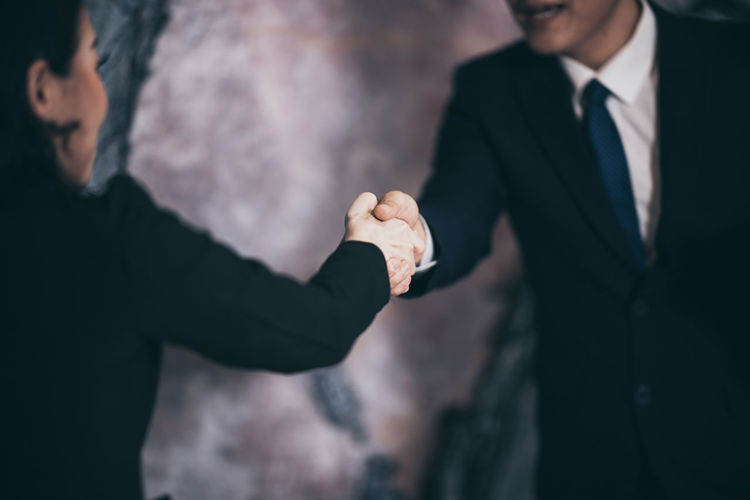 Midsection of business coworkers shaking hands in office