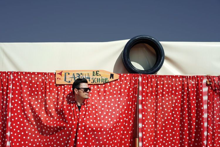 Man Hiding Behind Red Curtain Against Clear Sky