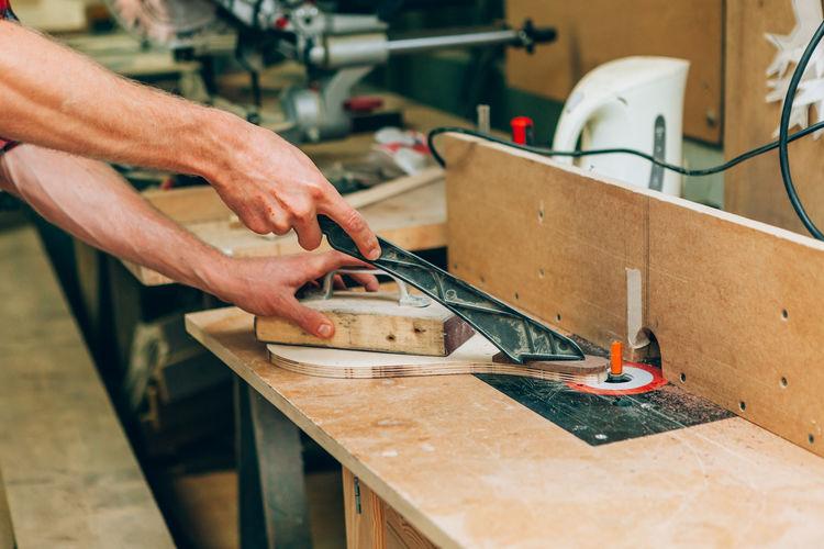 Carpenter hands working inside wood workshop