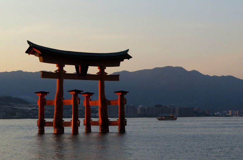 Torii gate in sea against sky during sunset