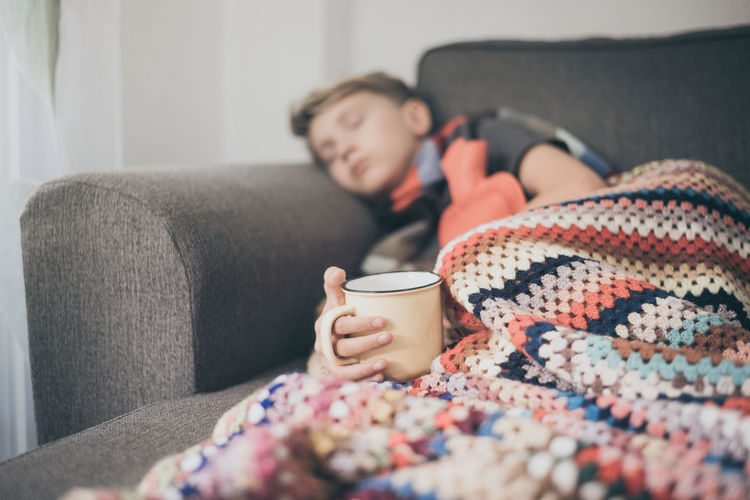 Boy sleeping on sofa with blanket while holding coffee cup in hand at home