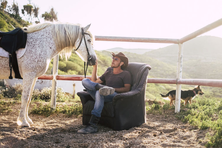 Cowboy Stroking Horse While Sitting On Armchair At Ranch