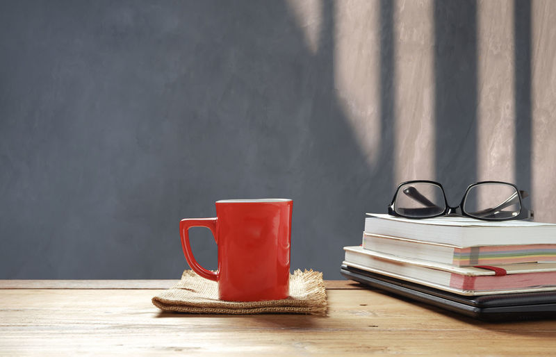 Coffee cup on table against wall