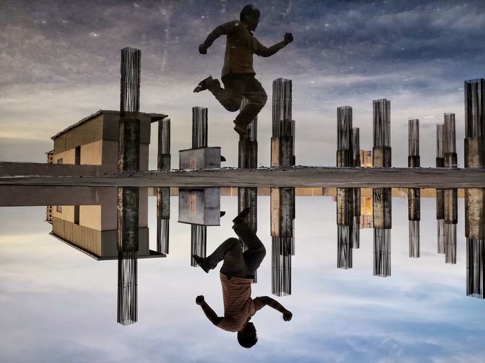 Symmetric view of man jumping by puddle against sky