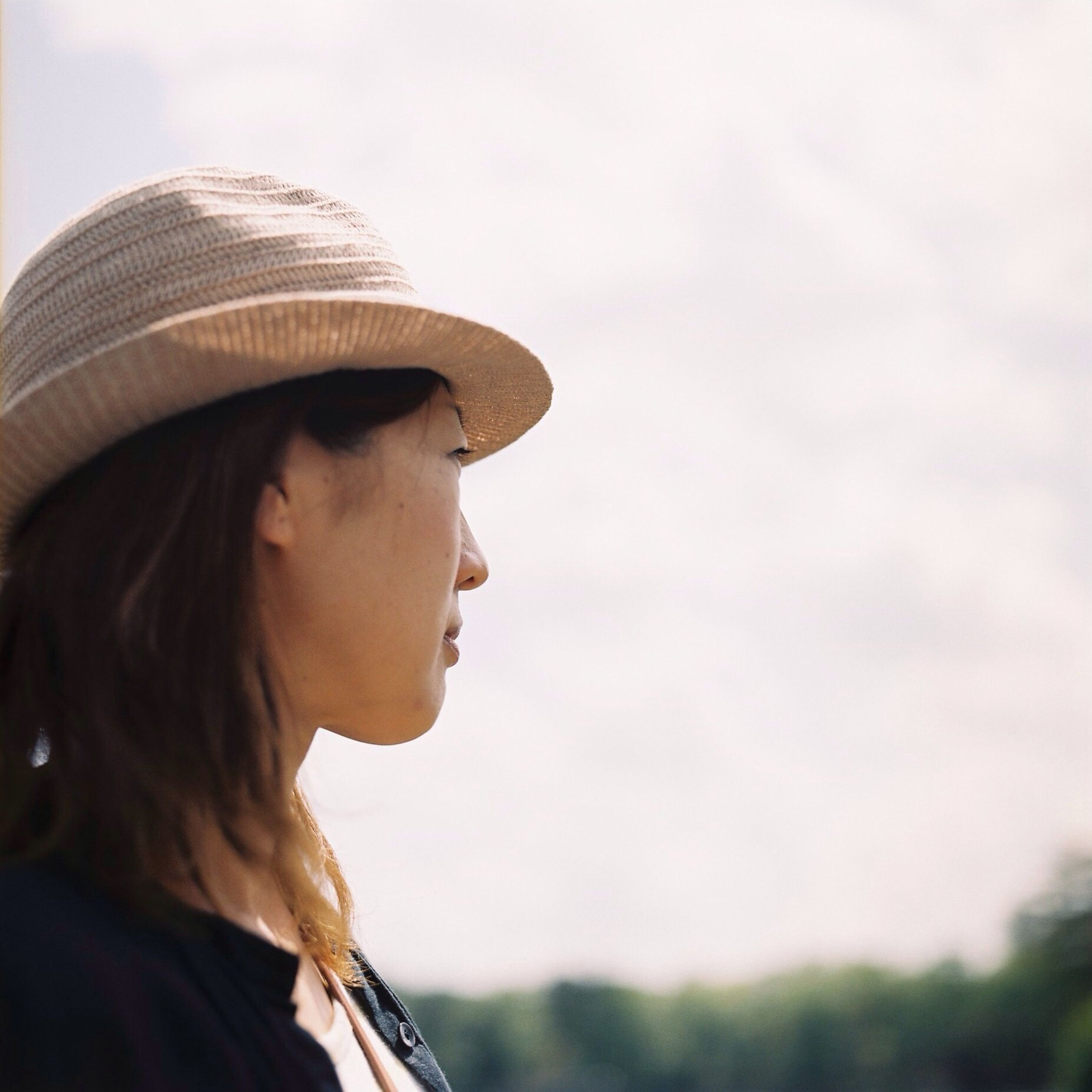 headshot, young adult, lifestyles, leisure activity, focus on foreground, sky, close-up, person, side view, head and shoulders, clear sky, portrait, waist up, sunglasses, day, outdoors, hat, young women
