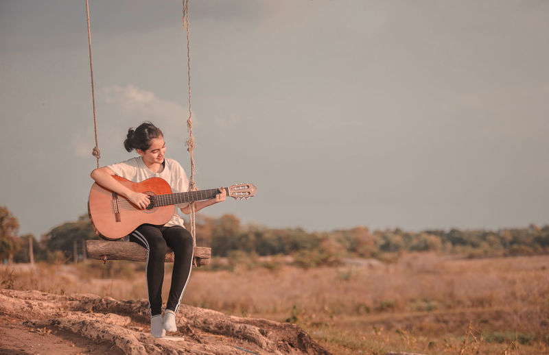 Full length of woman playing guitar on field against sky