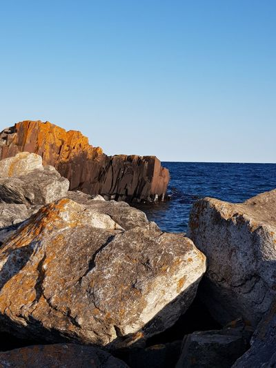 Rock Formations In Sea Against Clear Sky