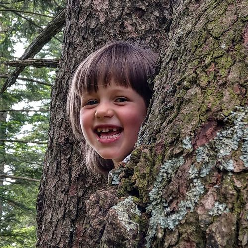 Portrait of cute smiling girl amidst tree trunk