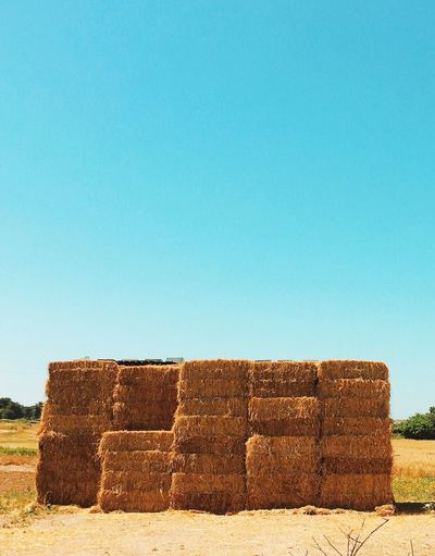 Hay stack in field against clear blue sky
