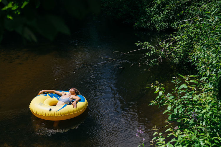 High angle view of woman with inflatable ring relaxing on river in forest