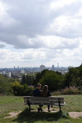 Couple looking out on London at Parliament Hill London Adult Architecture Arm Around Bench Built Structure Cityscape Cloud - Sky Couple - Relationship Looking At View Love Men Nature Outdoors Plant Positive Emotion Real People Rear View Relaxation Seat Sitting Sky Togetherness Two People Women