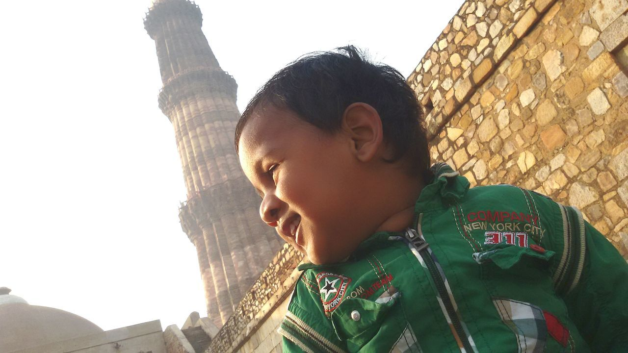 Low Angle View Of Happy Baby Against Qutub Minar