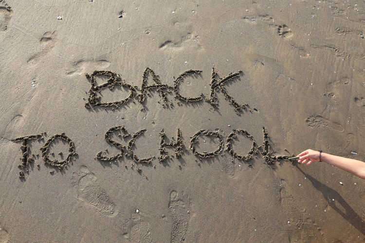 Back to School big written on the beach with child hand Children Hug Script Text Textured  Word Writer Back To School Back To School Text Childhood Education Hand Handsome Inscription Message Problem School School Life  Writting Young Adult