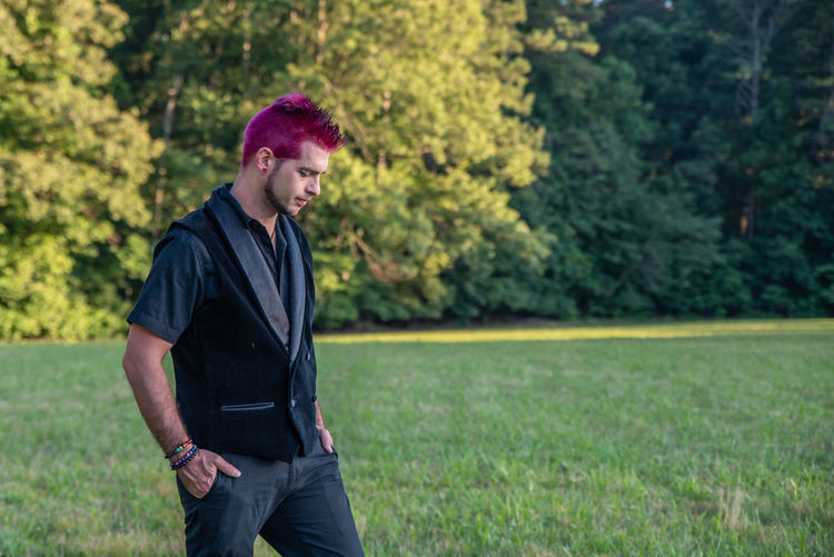 Man with dyed hair standing on grass land in park