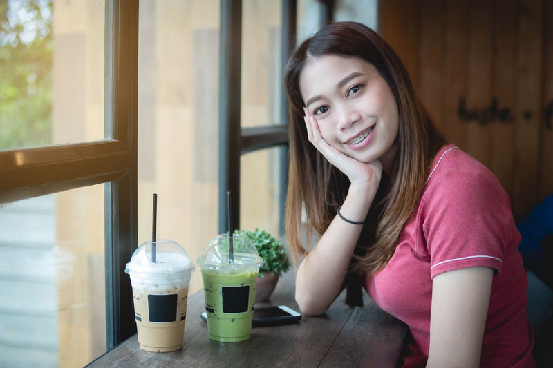 Portrait of smiling young woman sitting at restaurant table