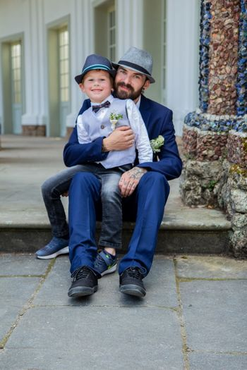 Full Length Portrait Of Father And Son Sitting Outdoors
