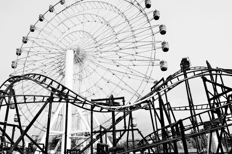Low Angle View Of Rollercoaster And Ferris Wheel At Amusement Park