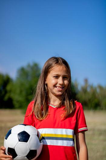 Portrait of smiling girl holding soccer ball against clear sky