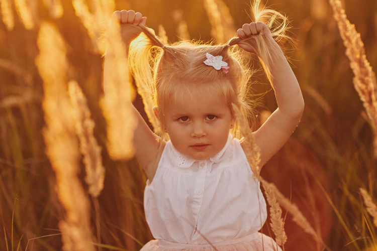 Portrait of cute girl with arms raised on field