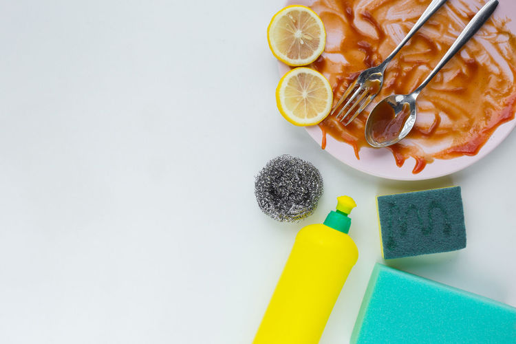 A dish with spoon and falk dirty after dinner , homework concept with washing liquid with sponge Food Food And Drink Citrus Fruit Still Life Freshness Fruit Lemon Indoors  Healthy Eating White Background SLICE No People Studio Shot Wellbeing Table Copy Space High Angle View Directly Above Close-up Ready-to-eat Temptation Dish Spoon Kitchen Utensil