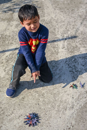 High angle view of boy pointing while playing with clothespin on land