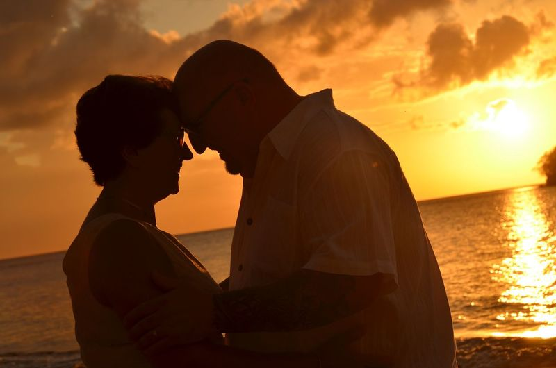 Side view of romantic couple looking at each other against sea during sunset