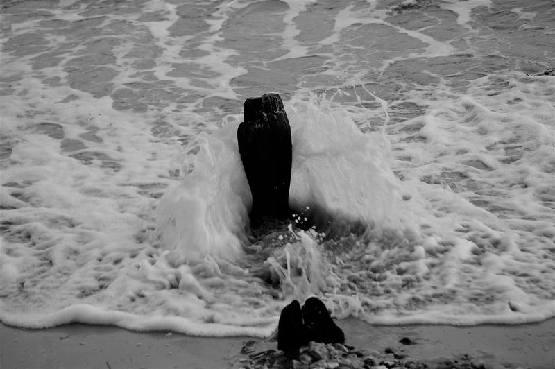Wave splashing up on old breakwater post. Water Sea Ocean Wet Wave Breaking Flowing Water Marine Splashing Motion Motion Capture Capture The Moment Force Pebbles On A Beach Beach Sand Tide Motion Blur No People Nature Beauty In Nature Power In Nature Scenics Nature Day Outdoors High Angle View Selective Focus Rear View Breakwater Wooden Post Eroded Worn Down Elements Salt Blackandwhite