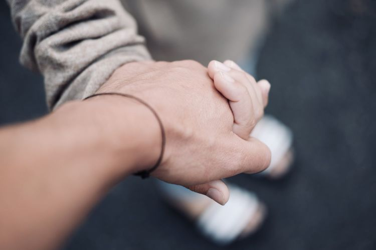 Cropped image of people holding hands