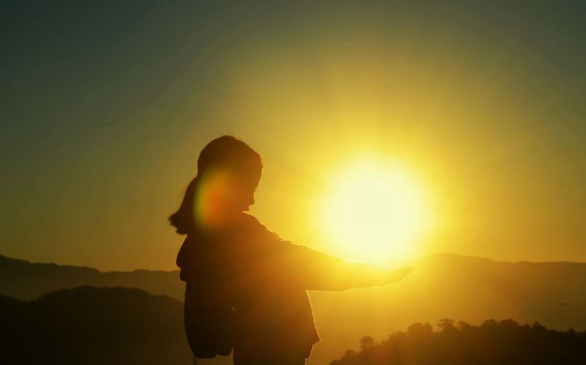 Optical illusion of silhouette woman holding sun against clear sky