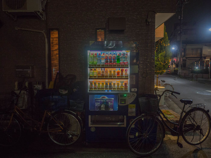 Bicycle parked on street against illuminated building at night
