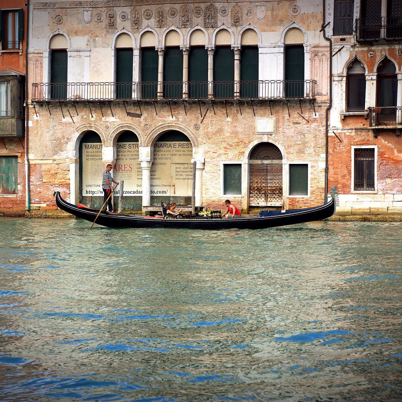 gondola - traditional boat, gondolier, canal, architecture, arch, transportation, tourism, nautical vessel, outdoors, men, travel destinations, building exterior, travel, gondola, day, built structure, real people, water, adult, adults only, people