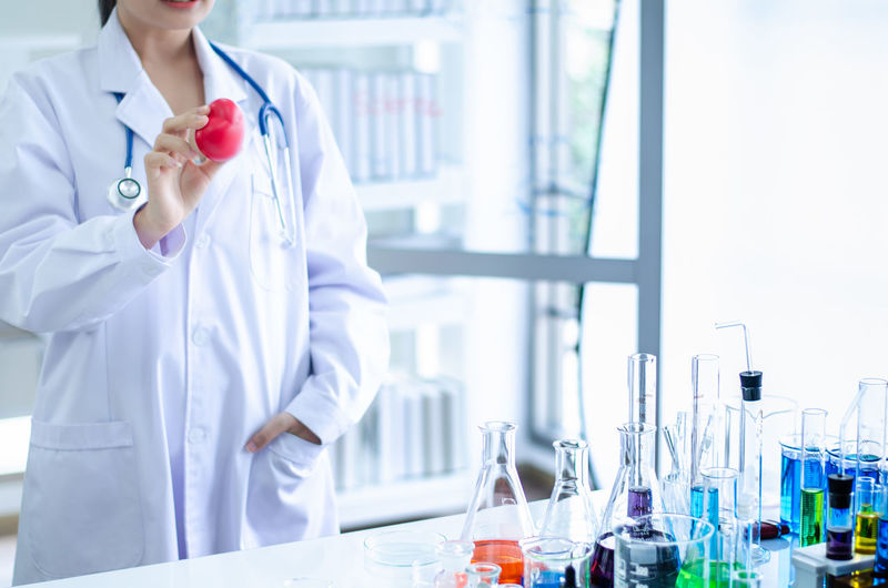 Midsection of female doctor standing by table in laboratory