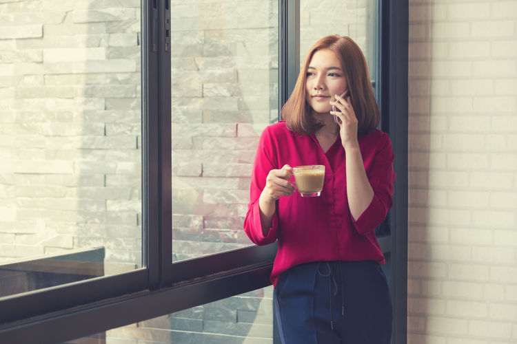 Businesswoman With Coffee Cup Talking On Smart Phone While Standing By Window At Office