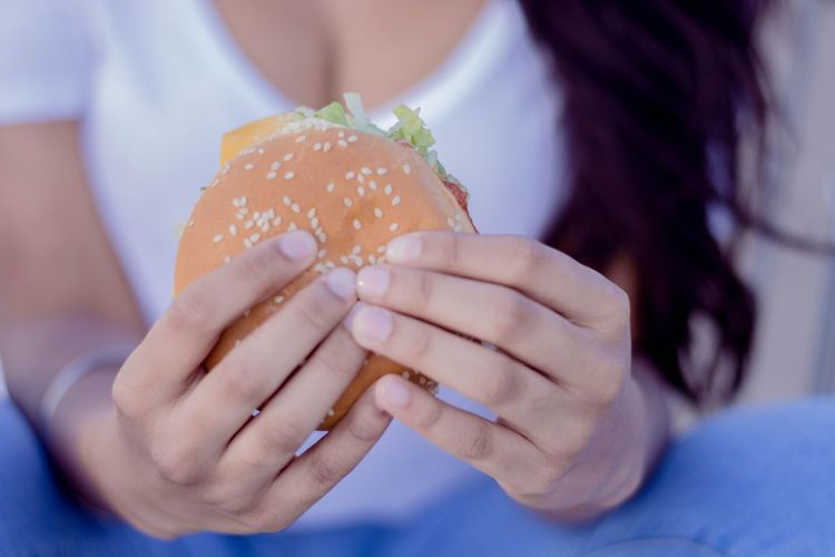 Midsection Of Woman Holding Hamburger